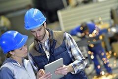 工程师在运作在数字式片剂的冶金工厂 免版税库存照片
