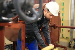 工程师在锅炉室转动闸式阀 加热的驻地的技术员操作员与管道一起使用 库存照片