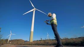 工程师在领域走在风车附近,拿着片剂 替代背景概念数字式能源例证太阳风 影视素材