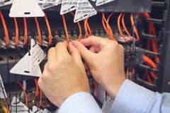 工程师在ISP网络服务提供商举行纤维插接线的数据处理中心 免版税库存图片