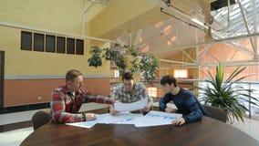 工程师坐在圆的木桌上并且谈论项目 股票视频