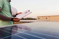 工程师审查发电性能图从是可选择能源的太阳电池板的,并且哪些是 图库摄影