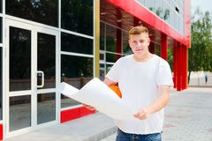 年轻工程师室外举行计划和建筑盔甲 库存图片