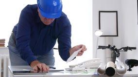 工程师工作在办公室在纸计算使用加法器并且写 影视素材