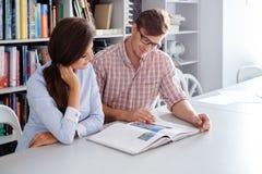 工程师快乐的夫妇获得读书的乐趣在建筑师演播室 免版税库存照片