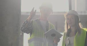 工程师或建筑师有一次讨论在看通过建筑计划的工地工作  contre jour 股票录像