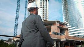 工程师或建造者检查和控制对象建设中 他由建造场所去, 股票录像