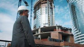 工程师或建造者检查和控制对象建设中 他由建造场所去, 股票视频