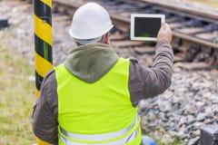 工程师摄制了与片剂个人计算机的铁路 免版税库存照片