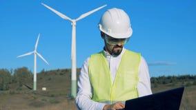 工程师操作在风车前面的一台膝上型计算机 干净,环境友好的能量概念 股票录像