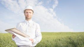 工程师是白色盔甲、衬衣和项目图画的建筑师在建筑站点在明亮的晴天 库存照片