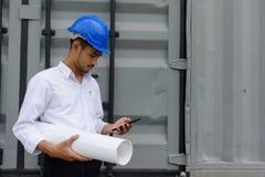 工程师检查在智能手机的建筑计划 库存照片