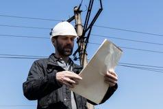 工程师检查电气系统谈携带无线电话,拿着图纸的审查员计划 免版税图库摄影