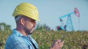 工程师油商与一个手机一起使用 油钻子,领域泵浦起重器 油田,油工作者运作 的treadled 影视素材