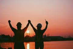 工程师的两三个配偶剪影握手的与快乐一起在码头 工作者和工程师 库存图片