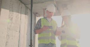 工程师设计师在大厦的屋顶站立建设中并且谈论计划和进展  影视素材