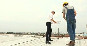 工程师谈论关于在屋顶的图纸 影视素材