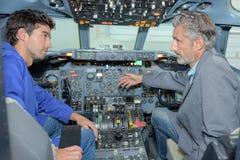 工程师谈话与驾驶舱航空器的实习生 免版税库存图片