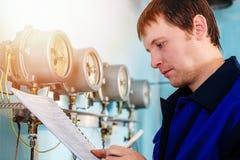 工程师,工作者登记传感器和压力表读书  供水和暖气控制  库存图片