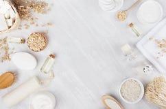 工艺品自然化妆用品-在柔光白色木桌,框架,平的位置上的白色奶油、油、毛巾和浴辅助部件 库存图片