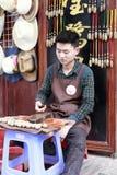 年轻工艺艺术家做并且卖石工艺品 库存照片
