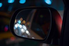 左翼镜子汽车在城市夜 免版税库存图片