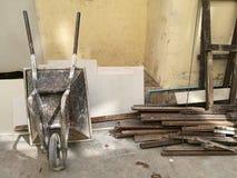 左角和搭乘木头的建筑金属独轮车推车常设上部在建造场所放弃大厦 库存照片