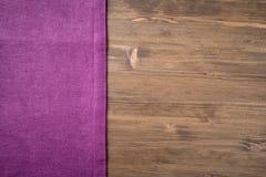从左边木桌的紫色餐巾 库存照片
