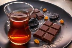 巧克力、修剪、葡萄干和茶在一块玻璃在一个黑色的盘子 库存照片