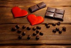 巧克力、咖啡豆和红心在自然木背景说谎 恋人的静物画 库存图片