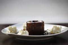 巧克力与奶油和糖浆的蛋白牛奶酥蛋糕 免版税库存图片