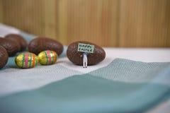 巧克力与微型愉快的复活节标志和词的复活节彩蛋 库存图片