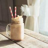 巧克力与打好的奶油的咖啡奶昔在灰色木背景的玻璃金属螺盖玻璃瓶服务 夏天甜点饮料 方形的imag 图库摄影