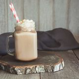 巧克力与打好的奶油的咖啡奶昔在灰色木背景的玻璃金属螺盖玻璃瓶服务 夏天甜点饮料 正方形 库存图片