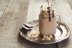 巧克力与打好的奶油的咖啡奶昔在灰色木背景的玻璃金属螺盖玻璃瓶服务 夏天甜点饮料 库存照片