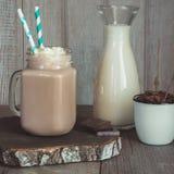 巧克力与打好的奶油的咖啡奶昔在灰色木背景的玻璃金属螺盖玻璃瓶服务 甜饮料 方形的图象 库存图片