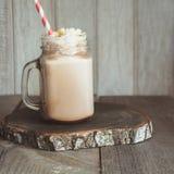 巧克力与打好的奶油的咖啡奶昔在灰色木背景的玻璃金属螺盖玻璃瓶服务 玻璃水瓶柑橘饮料冰橙色夏天水 方形的图象 免版税库存照片