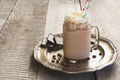 巧克力与打好的奶油的咖啡奶昔在葡萄酒木背景的玻璃金属螺盖玻璃瓶服务 甜饮料 免版税库存图片