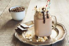 巧克力与打好的奶油的咖啡奶昔在葡萄酒木背景的玻璃金属螺盖玻璃瓶服务 甜饮料 库存图片