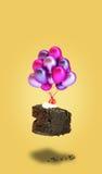 巧克力与气球的樱桃蛋糕在黄色背景 免版税库存照片