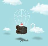 巧克力与降伞的樱桃蛋糕在与文本的蓝天背景 免版税库存照片