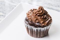 巧克力与ganache巧克力奶油的杯子蛋糕在白方块板材 图库摄影