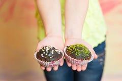 巧克力两块杯形蛋糕在childs手上 库存照片