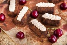 巧克力兰姆酒球蛋糕装饰用奶油色和新鲜的樱桃 免版税库存照片