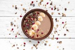 巧克力可可粉香蕉蛋白质有格兰诺拉麦片和石榴种子的圆滑的人碗 顶视图 库存照片