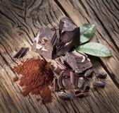 巧克力和可可子在木头 免版税库存图片