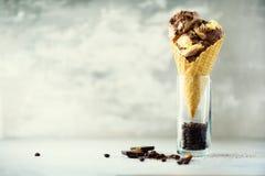 巧克力和咖啡在奶蛋烘饼锥体的冰淇凌用在灰色石背景的咖啡豆 夏天食物概念,拷贝 库存照片