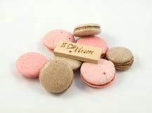 巧克力和桃红色macarons混乱被安排的和有题字的一个委员会我爱妈咪 一个愉快的母亲节题材 免版税库存图片