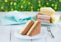 巧克力和黄油雪芳蛋糕片断在板材的快餐的 免版税库存照片