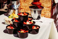 巧克力喷泉和切片草莓香蕉在黑杯子在一张白色桌上,可口甜点点心,街道食物 免版税库存照片